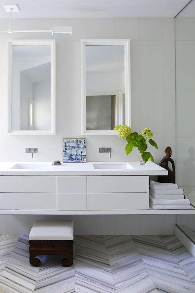 "<p>A sleek vanity and chevron patterned floor steal the show in a modern <a href=""https://www.elledecor.com/design-decorate/house-interiors/g1039/neutral-palette-washington-dc-apartment/"" target=""_blank"">Washington, D.C., home</a> designed by Darryl Carter.<br></p>"