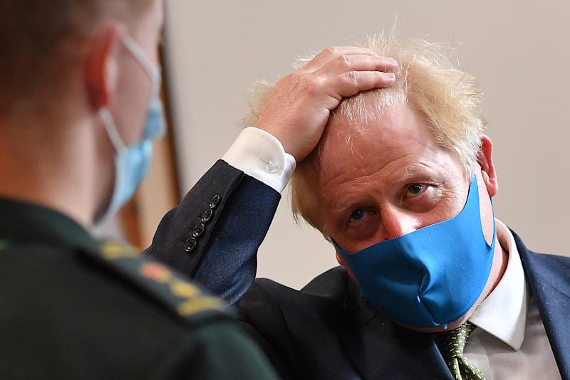 Prime Minister Boris Johnson, wearing a face mask, talks with a paramedic during a visit to the headquarters of the London Ambulance Service NHS Trust.