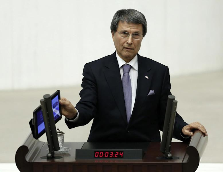 Yusuf Halacoglu, a deputy from the opposition Nationalist Action Party, MHP, plays a recording of a wiretapped conversation allegedly between Prime Minister Recep Tayyip Erdogan and a manager of a television station that reportedly was leaked onto the Internet, during a parliamentary debate late Wednesday, Feb. 5, 2014, shortly before legislators approved measures that would tighten government controls over the Internet. With a show of hands, the legislators late Wednesday endorsed allowing Turkey's telecommunications authority to block websites for a privacy violation without a prior court decision.(AP Photo)