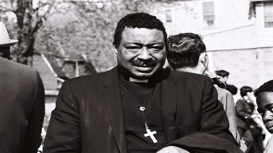 a reverend is seen in a black and white photo wearing a clerical collar with a cross around his neck