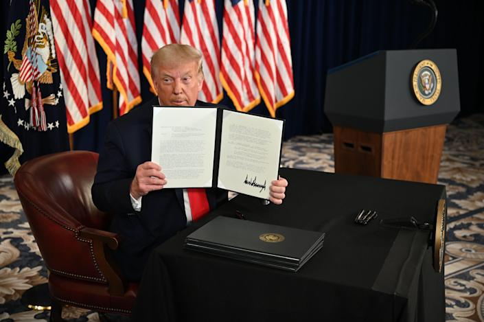 US President Donald Trump signs executive orders extending coronavirus economic relief, during a news conference in Bedminster, New Jersey, on August 8, 2020. (Photo by JIM WATSON/AFP via Getty Images)