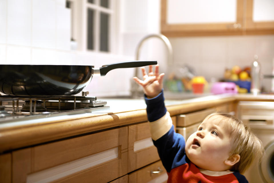 Young boy reaching for a hot pan on a hob