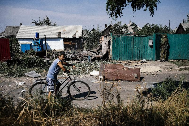 A man walks next to his bicycle next to damaged houses and walls after shelling in Donetsk on August 22, 2014 (AFP Photo/Dimitar Dilkoff)