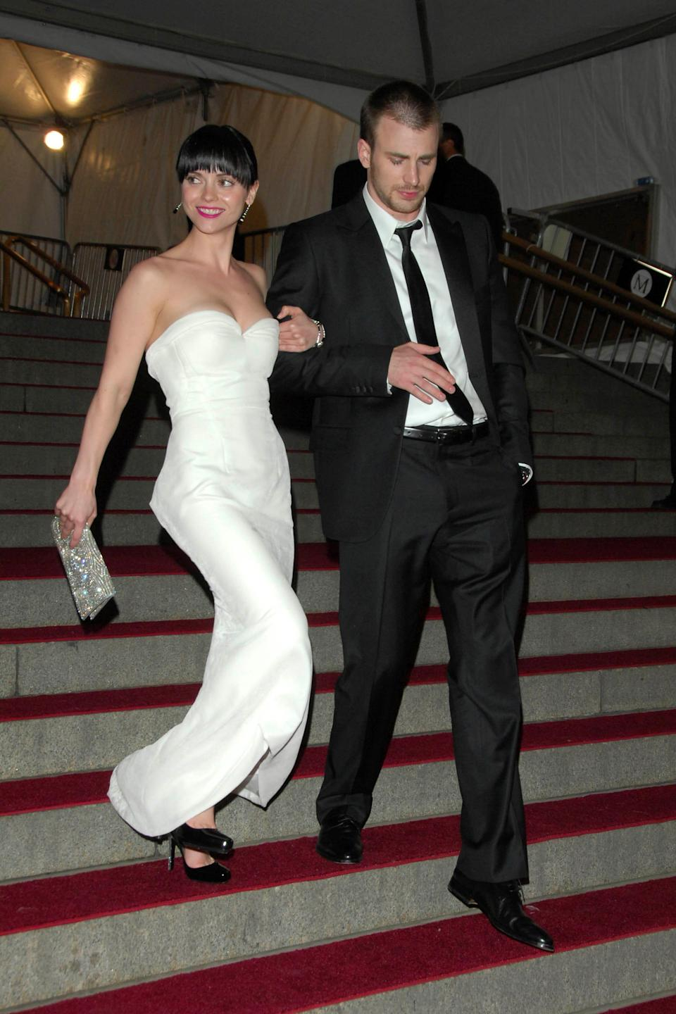 Christina Ricci wears a white dress and walks down a flight of stairs with Chris Evans, who wears a black suit.