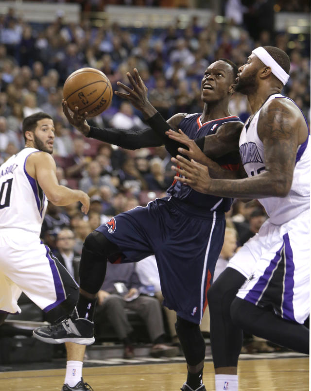 Atlanta Hawks guard Dennis Schroder, of Germany, center, drives to the basket against Sacramento Kings center DeMarcus Cousins, right, during the first quarter of an NBA basketball game in Sacramento, Calif., Tuesday, Nov. 5, 2013. (AP Photo/Rich Pedroncelli)