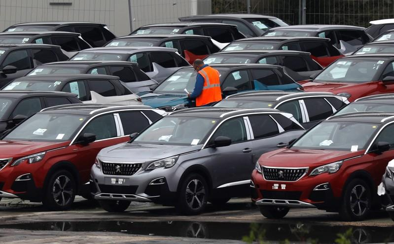 A worker checks cars at the PSA Peugeot Citroen plant in Poissy, near Paris