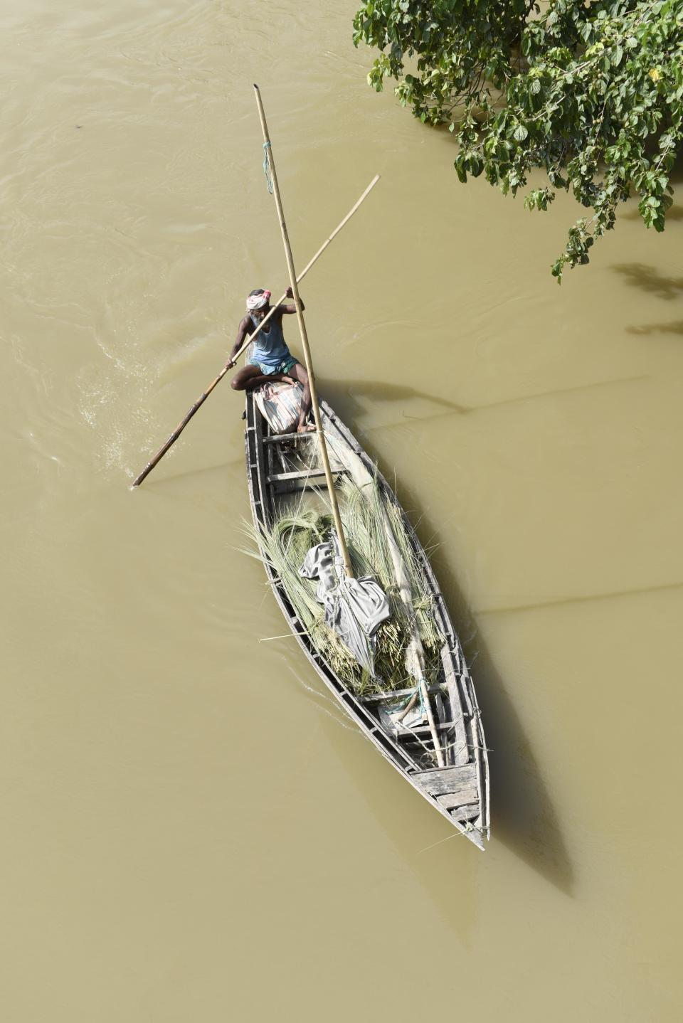 Villager uses a boat to move across a flooded area in a flood effected village in Morigaon district of Assam in India on Friday, 17 July 2020. (Photo by David Talukdar/NurPhoto via Getty Images)