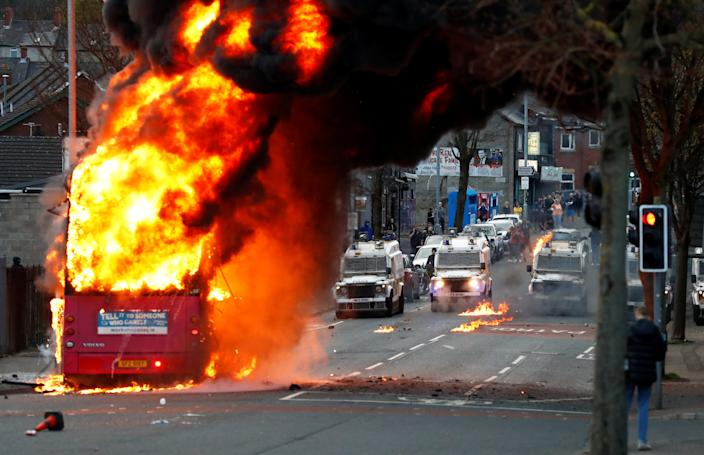Police vehicles are seen behind a hijacked bus burning on Shankill Road as protests continue in Belfast, Northern Ireland, April 7, 2021. REUTERS/Jason Cairnduff TPX IMAGES OF THE DAY