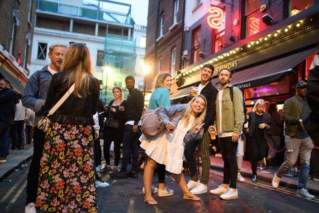 People eat and drink outdoors in Soho, London, as coronavirus lockdown restrictions are eased across England.