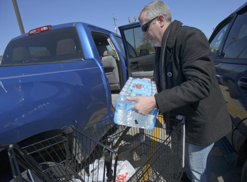 New Orleans resident Bryant Faul loads bottled water from Rouses Supermarket in New Orleans , La., Sunday, March 3, 2013. Widespread loss of water pressure was reported and the city advised residents in most of the city to boil their water. (AP Photo/Matt Hinton)