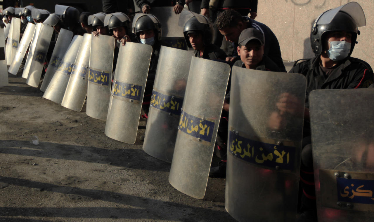 Egyptian riot police rest during clashes with anti-government protesters, not seen, near Tahrir Square, Cairo, Egypt,Tuesday, Jan. 29, 2013. Intense fighting for days around central Tahrir Square engulfed two landmark hotels and forced the U.S. Embassy to suspend public services on Tuesday. (AP Photo/Khalil Hamra)