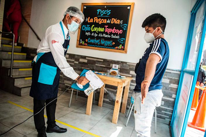 """A waiter disinfects a customer as he enters a restaurant in Lima on July 20, 2020. <p class=""""copyright"""">ERNESTO BENAVIDES/AFP via Getty Images</p>"""