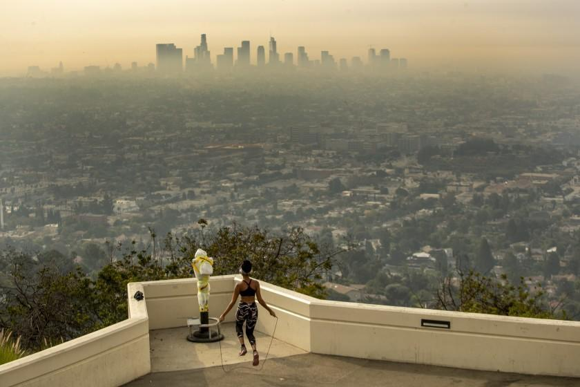 LOS ANGELES, CA - SEPTEMBER 17: Los Angeles resident Carmen Green jumps rope at a closed Griffith Observatory where she found a quiet nook to exercise in spite of dense smoke from Southern California wildfires choking the L.A. Basin on Thursday, Sept. 17, 2020 in Los Angeles, CA. (Brian van der Brug / Los Angeles Times)
