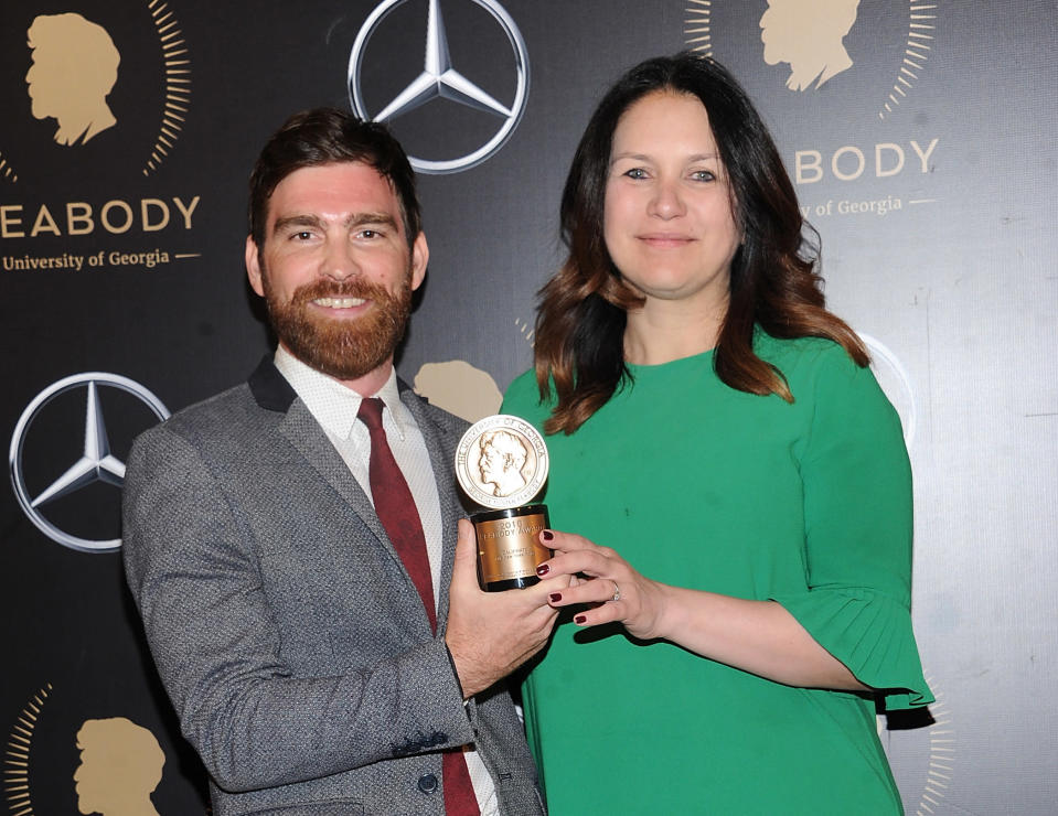 """FILE - Andy Mills, left, and Rukmini Callimachi hold the award for their 2018 podcast """"Caliphate"""" at the 78th annual Peabody Awards in New York on May 18, 2019. The New York Times says it was wrong to trust the story of a Canadian man whose claims of witnessing and participating in atrocities as a member of the Islamic State was a central part of its award-winning 2018 podcast """"Caliphate."""" The 12-part series won a Peabody Award and was a Pulitzer Prize finalist. But it began to unravel when Canadian authorities in September arrested Shehroze Chaudhry on charges of perpetrating a terrorist hoax. He was included in the podcast under the alias Abu Huzayfah. The Times said its journalists should have done a better job vetting him, and not included his story as part of the podcast. (Photo by Brad Barket/Invision/AP, FIle)"""