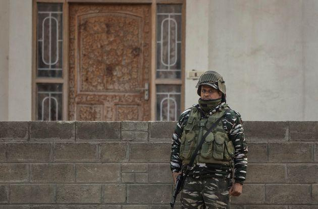 A soldier stands guard as National Investigation Agency personnel search the premises of AFP's Kashmir correspondent Parvaiz Bukhari on the outskirts of Srinagar on October 28, 2020.