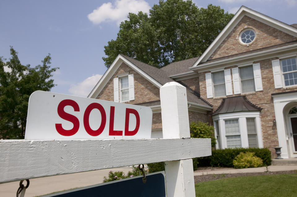 Sold house sign in Midwest suburban setting. Focus on sign.