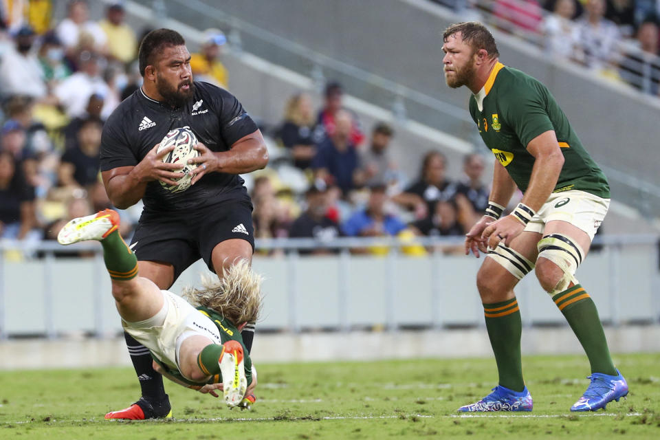 New Zealand's Nepo Laulala is tackled by South Africa's Faf de Klerk as South Africa's Duane Vermeulen, right, watches during the Rugby Championship test match between the Springboks and the All Blacks in Townsville, Australia, Saturday, Sept. 25, 2021. (AP Photo/Tertius Pickard)