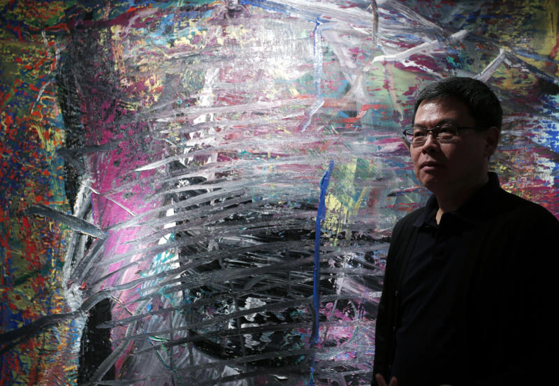 In this photo taken on Monday, April 2, 2012, Indonesian-Chinese farming tycoon Budi Tek poses in front of a painting by Gerhard Richter during an auction preview in Hong Kong. Tek is set to open the De Museum in Shanghai next year featuring Asian and Western contemporary art, after opening his first in Indonesia's capital Jakarta in 2008. While Asia's new generation of wealthy are usually better known for splashing out on extravagant toys such as private jets, mega-sized yachts and supercars, some instead have built big art collections and now aspire to showcase their refined sensibility to a wider audience. (AP Photo/Vincent Yu)