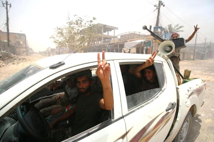 Fighters from the Popular Mobilisation units, supporting Iraqi government forces, patrol a street in Fallujah in June after Iraqi forces retook the city from IS (AFP Photo/Haidar Mohammed Ali)