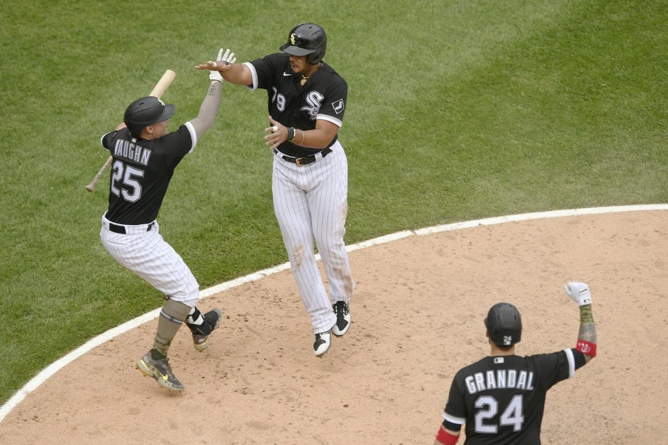 Chicago White Sox's Jose Abreu (79) celebrates with teammate Andrew Vaughn (25) after sliding into home plate safely on a wild pitch to defeat the Kansas City Royals in a baseball game Sunday, May 16, 2021, in Chicago. (AP Photo/Paul Beaty)