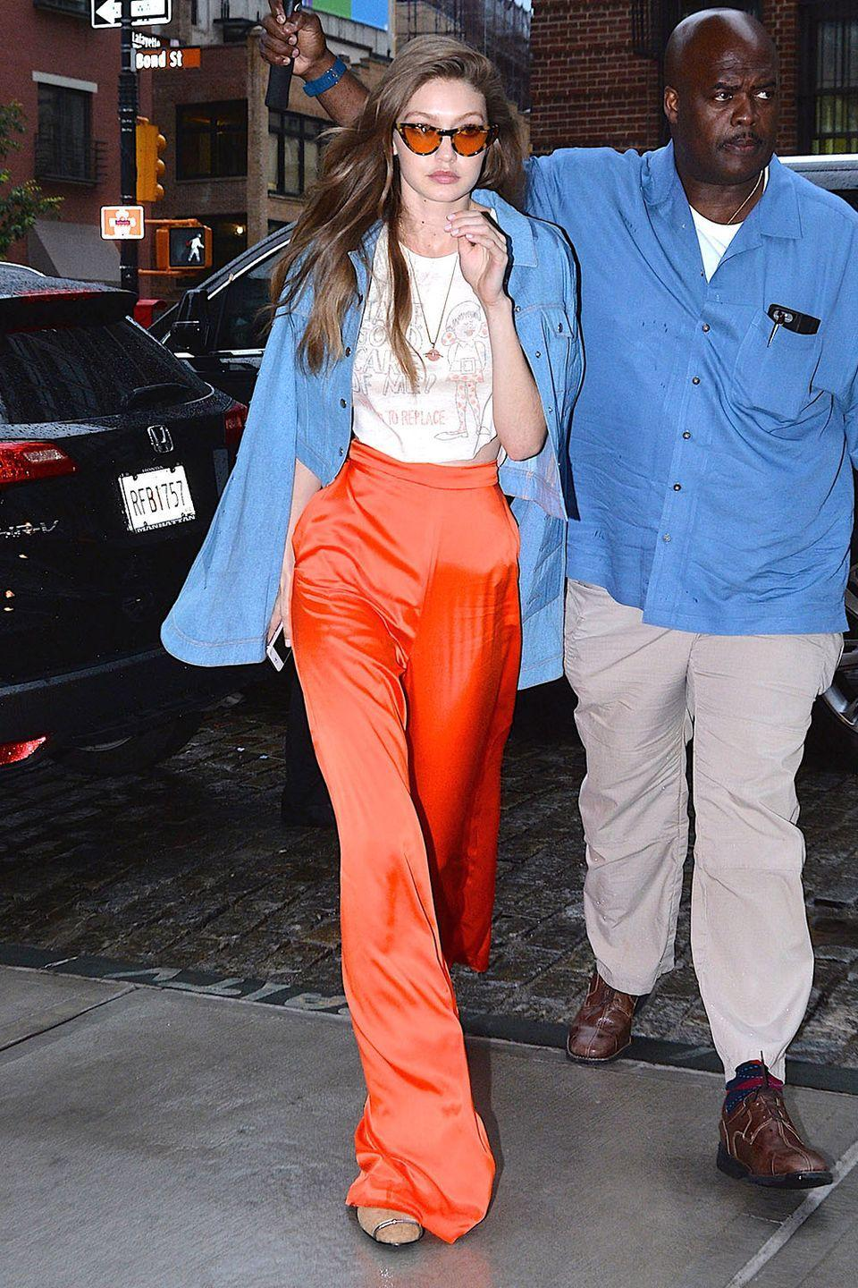 <p>In a baby blue jacket, high-waisted Stella McCartney bright orange pants, retro shades, and a graphic t-shirt while out in New York City. </p>