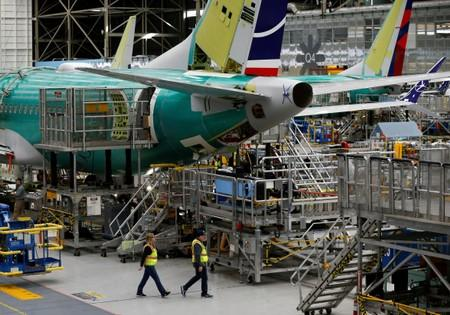 FILE PHOTO: Employees walk by the end of a 737 Max aircraft at the Boeing factory in Renton