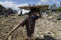 A resident carries a television across debris and floods at the typhoon-damaged Kasiglahan village in Rodriguez, Rizal province, Philippines on Friday, Nov. 13, 2020. Thick mud and debris coated many villages around the Philippine capital Friday after Typhoon Vamco caused extensive flooding that sent residents fleeing to their roofs and killing dozens of people. (AP Photo/Aaron Favila)