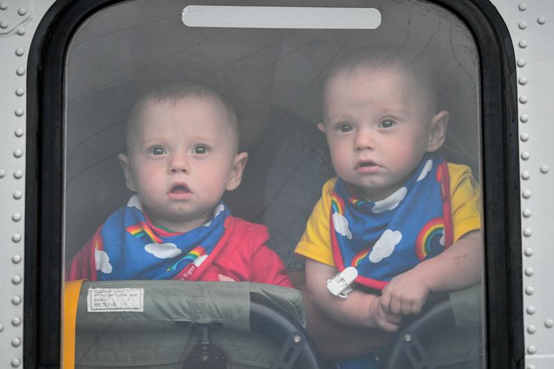 Twin boys Ruben (left) and Jenson Powell peer through a helicopter window as they celebrate their first birthday by meeting HM Coastguard crews for the first time since Jennie was airlifted in a helicopter to Oxford from Cornwall after she went into labour at 22 weeks with her twins, giving birth the youngest surviving pre-term twin boys born in Britain. (Photo by Ben Birchall/PA Images via Getty Images)