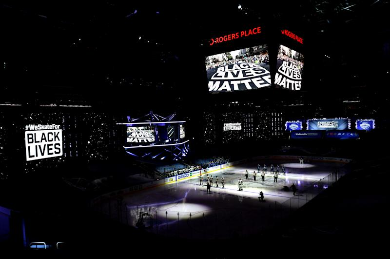 """A general view of the Vegas Golden Knights and the Vancouver Canucks players standing on the ice during pregame as """"Black Lives Matter"""" is seen on arena screens as the NHL unite in the cause to end racism before Game Three of the Western Conference Second Round during the 2020 NHL Stanley Cup Playoffs"""
