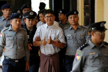 Detained Reuters journalist Wa Lone is escorted by police before a court hearing in Yangon, Myanmar April 20, 2018. REUTERS/Ann Wang