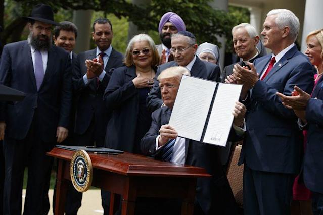 President Trump holds the executive order aimed at easing an IRS rule limiting political activity for churches, on May 4, 2017, in the White House Rose Garden. (Photo: Evan Vucci/AP)