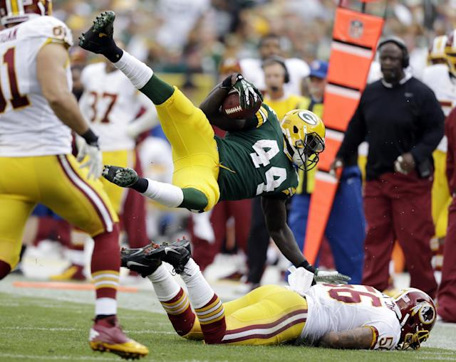 Green Bay Packers' James Starks is tripped up on a run during the second half of an NFL football game against the Washington Redskins Sunday, Sept. 15, 2013, in Green Bay, Wis. (AP Photo/Tom Lynn)