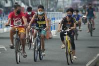 Boys wearing face masks to prevent the spread of the coronavirus ride their bikes outside Manila's COVID-19 Field Hospital, Philippines on Thursday, Sept. 2, 2021. The Philippines has recorded over two million COVID-19 cases as infections continue to rise in the country. (AP Photo/Aaron Favila)