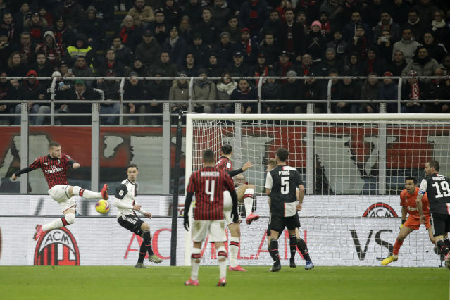 AC Milan's Ante Rebic, left, scores his side's opening goal during an Italian Cup soccer match between AC Milan and Juventus at the San Siro stadium, in Milan, Italy, Thursday, Feb. 13, 2020. (AP Photo/Luca Bruno)