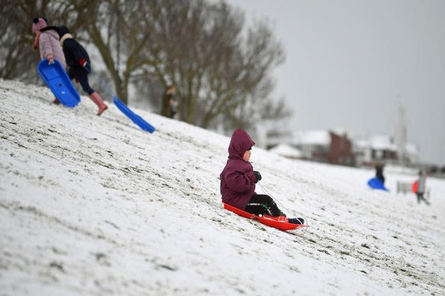 A child goes sledging in the snow