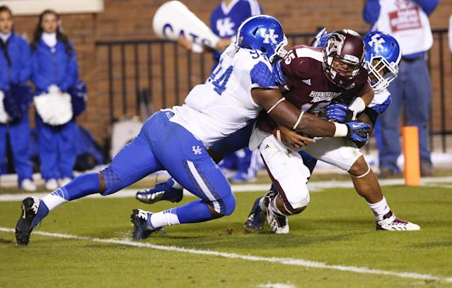 Mississippi State quarterback Dak Prescott (15) is tackled for a loss by Kentucky defensive ends Za'Darius Smith (94) and Alvin Dupree in the second half of their NCAA college football game at Davis Wade Stadium in Starkville, Miss., Thursday, Oct. 24, 2013. Mississippi State won 28-22. (AP Photo/Rogelio V. Solis)