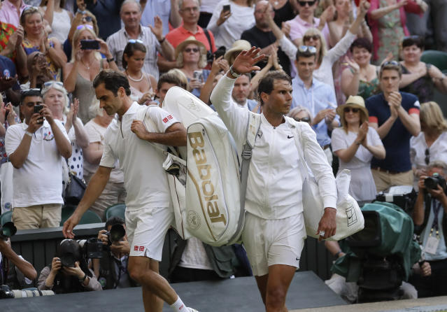 Switzerland's Roger Federer, left, leaves the court after beating Spain's Rafael Nadal, right, in a Men's singles semifinal match on day eleven of the Wimbledon Tennis Championships in London, Friday, July 12, 2019. (AP Photo/Kirsty Wigglesworth)