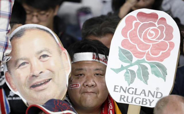 A fan holds a photo of England coach Eddie Jones before the Rugby World Cup final at International Yokohama Stadium between England and South Africa in Yokohama, Japan, Saturday, Nov. 2, 2019. (AP Photo/Aaron Favila)