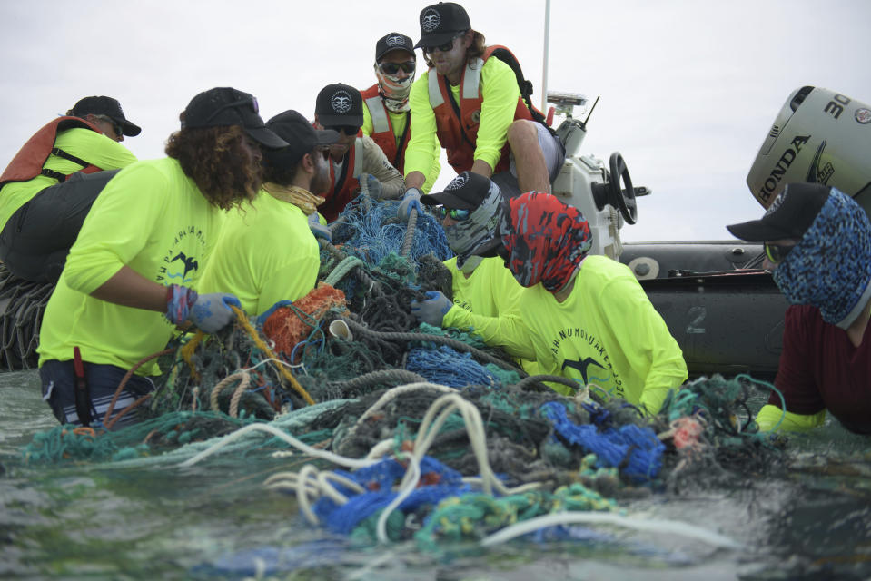 In this April 8, 2021 photo provided by Matthew Chauvin, workers with the Papahanaumokuakea Marine Debris Project load fishing nets onto a small boat on Midway Atoll in the Northwestern Hawaiian Islands. A crew has returned from the remote Northwestern Hawaiian Islands with a boatload of marine plastic and abandoned fishing nets that threaten to entangle endangered Hawaiian monk seals and other marine animals on the tiny, uninhabited beaches stretching for more than 1,300 miles north of Honolulu. (Matthew Chauvin, Papahanaumokuakea Marine Debris Project via AP)
