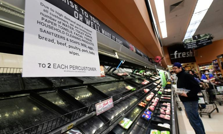 A sign announces a two-item limit for certain items as people shop for food in Monterey Park, California
