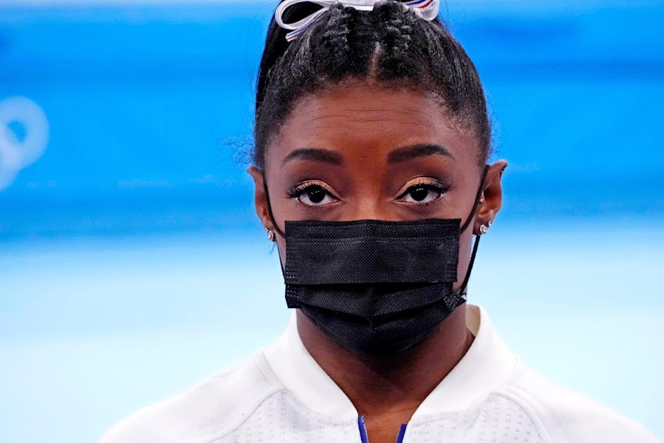 Simone Biles looks on after pulling out of the women's gymnastic team final.