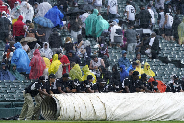 The Chicago White Sox grounds crew puts a tarp on the field during a rain delay in the third inning of a baseball game against the Seattle Mariners in Chicago, Saturday, June 26, 2021. (AP Photo/Nam Y. Huh)
