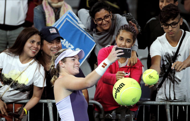 Catherine McNally of the United States takes a selfie with spectators after defeating Australia's Samantha Stosur in their first round singles match at the Australian Open tennis championship in Melbourne, Australia, Monday, Jan. 20, 2020. (AP Photo/Andy Wong)