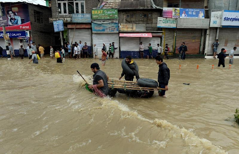 Indian Kashmiri people make their way along a flooded street in Srinagar, in India's northern Jammu and Kashmir province, on September 9, 2014 (AFP Photo/Punit Paranjpe)