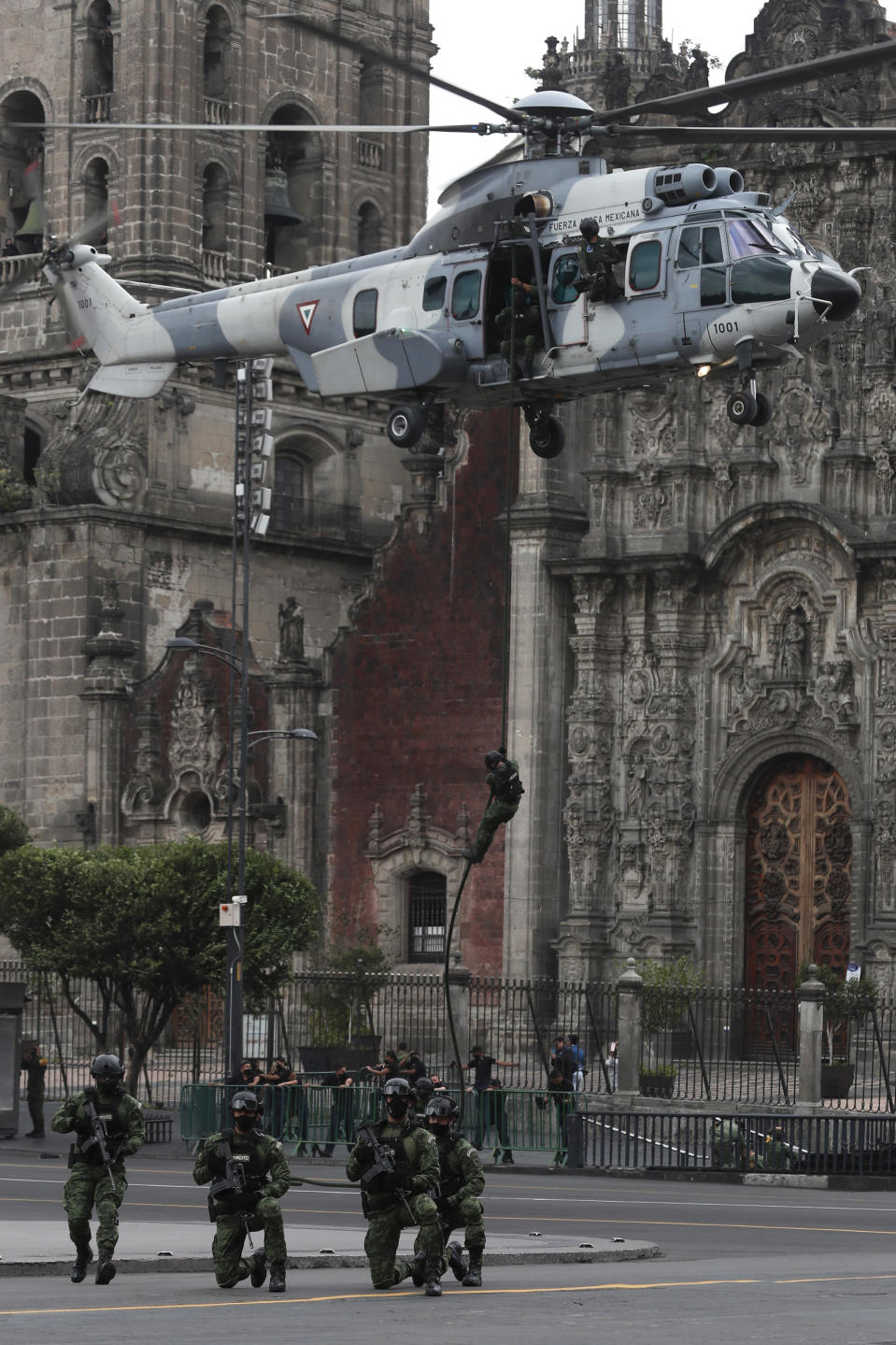 A paratrooper repels from a helicopter hovering over Mexico City's main square, known as the Zocalo, during the annual Independence Day military parade, Wednesday, Sept. 16, 2020. Mexicans celebrated their Independence Day without big public ceremonies for the first time in 153 years Tuesday night due to restrictions on public gatherings caused by the coronavirus pandemic. (AP Photo/Marco Ugarte)