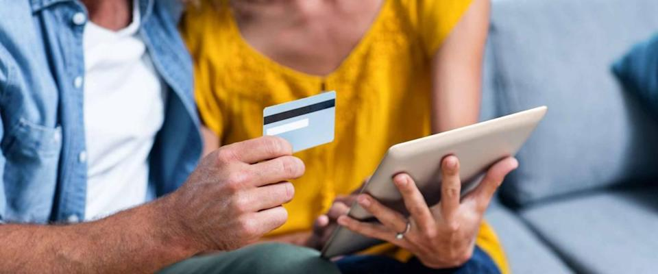 Couple sitting on sofa and doing online shopping on digital tablet