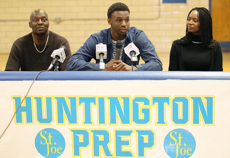 Huntington Prep basketball player Andrew Wiggins, center, flanked by his parents Mitchell Wiggins and Marita Payne-Wiggins, as he announces his commitment to the University of Kansas during a ceremony, Tuesday, May 14, 2013, at St. Joseph High School in Huntington W.Va. The Canadian star, a top prospect, averaged 23.4 points and 11.2 rebounds per game this season for West Virginia's Huntington Prep. (AP Photo/The Herald-Dispatch, Sholten Singer)
