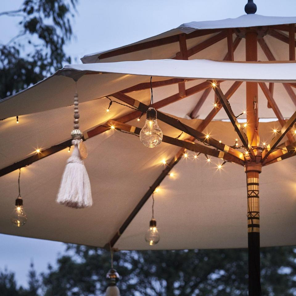 """<p>Outdoor lights offer a quick, simple and cheap way to bring a pretty glow to a patio and beyond – and there are so many styles available. Solar garden lights are popular, or you can opt for outdoor battery lights which include string lights and lanterns.</p><p>If you're using fairy lights or festoon lights, you can style them through trees or shrub branches, attach them to fences and furniture, or suspend them from canes stuck into the ground. Stringing fairy lights across a pergola or arch or even around a parasol, always looks wonderful and creates a perfect setting for alfresco dining.</p><p><strong>Pictured: </strong>80 LED Battery Operated Parasol Lights, <a href=""""https://go.redirectingat.com?id=127X1599956&url=https%3A%2F%2Fwww.lights4fun.co.uk%2Fproducts%2F80-led-battery-operated-parasol-lights&sref=https%3A%2F%2Fwww.redonline.co.uk%2Finteriors%2Feditors_choice%2Fg35933369%2Fgarden-ideas-on-a-budget%2F"""" rel=""""nofollow noopener"""" target=""""_blank"""" data-ylk=""""slk:Lights4Fun"""" class=""""link rapid-noclick-resp"""">Lights4Fun</a></p>"""