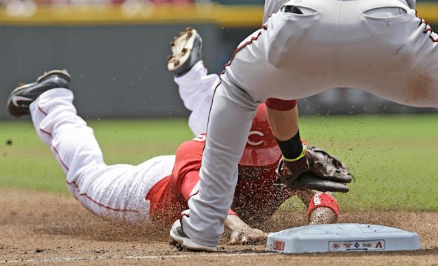 Cincinnati Reds' Ramon Santiago is tagged out by Arizona Diamondbacks third baseman Martin Prado, trying to steal third base in the third inning of a baseball game, Wednesday, July 30, 2014, in Cincinnati. (AP Photo/Al Behrman)
