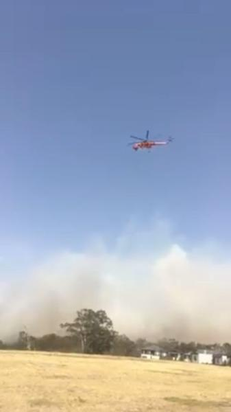 A water bomber helicopter flies over as the bushfires continue in Bundoora
